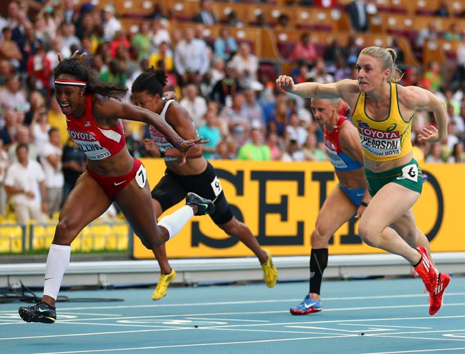 Brianna Rollins (left) of the United States crosses the line to win gold ahead of Sally Pearson (right) of Australia