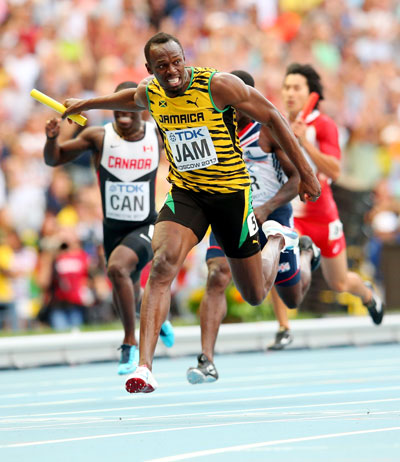 Usain Bolt of Jamaica crosses the line first win gold in the Men's 4x100 metres final