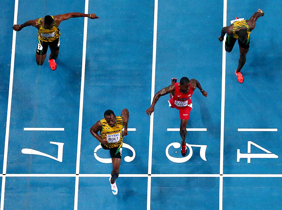 Usain Bolt (second left) wins the 100m ahead of  Justin Gatlin (red) of the US