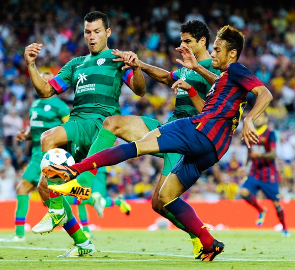 Neymar of FC Barcelona shoots towards goal under a challenge by Lenvate UD players