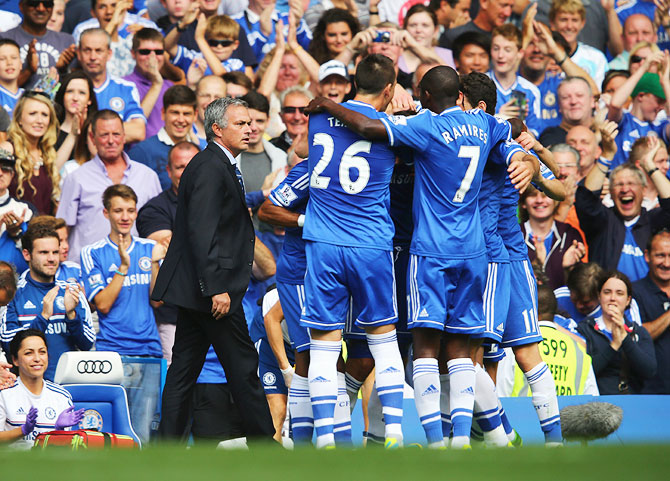 Chelsea players celebrate as goals as manager Jose Mourinho looks on