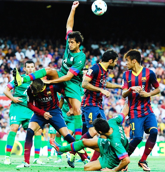 Gerard Pique of FC Barcelona duels for a high ball with Hector Rodas of Levante