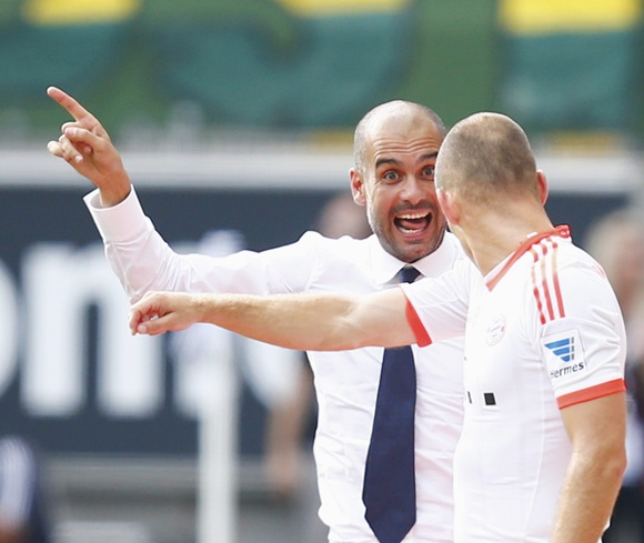 Bayern Munich's coach Pep Guardiola (left) instructs Arjen Robben