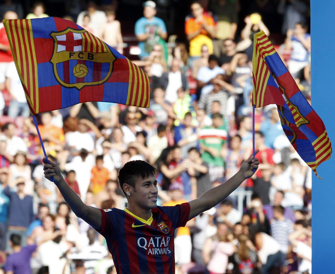 Neymar waves flags Barcelona's flags as he acknowledges the fans at his presentation