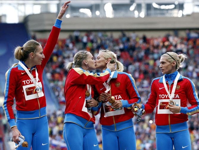 Tatyana Firova and Kseniya Ryzhova of Russia kiss on the podium as team mates Yulia Gushchina and Antonina Krivoshapka look on