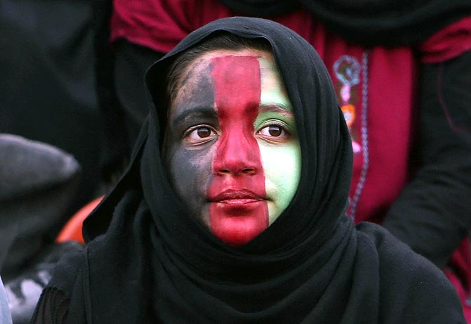 An Afghan girl watches a friendly soccer match between Afghanistan and Pakistan in Kabul