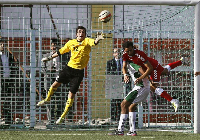 Pakistan goalkeeper Saqib Hanif jumps to make a save