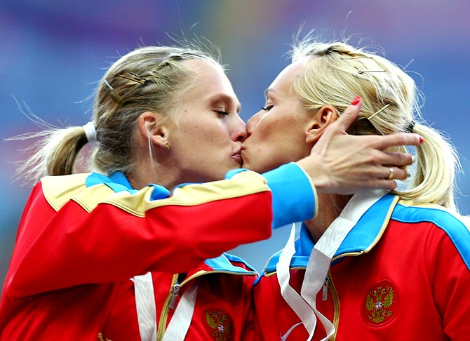 Tatyana Firova and Kseniya Ryzhova of Russia kiss on the podium during the medal ceremony for the women's 4x400 metres relay at the World Athletics Championships in Moscow