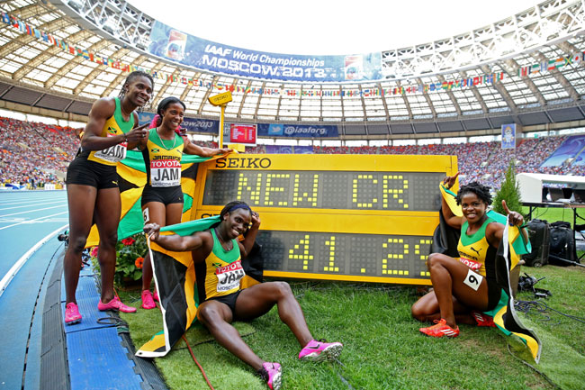 Gold medalists Carrie Russell, Shelly-Ann Fraser-Pryce, Schillonie Calvert and Nickiesha Wilson   of Jamaica pose with the clock after setting a new championship record
