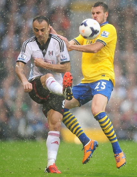 Dimitar Berbatov of Fulham and Carl Jenkinson of Arsenal tussle for the ball