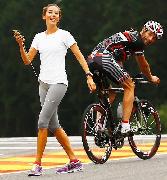 Mark Webber of Red Bull Racing rides his bike past Jenson Buttons girlfriend Jessica Michibata