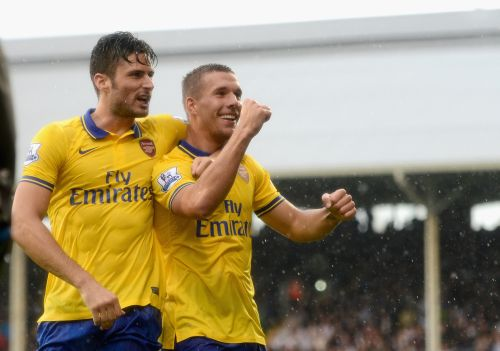 Lukas Podolski of Arsenal (R) celebrates scoring his side's third goal with team mate Olivier Giroud
