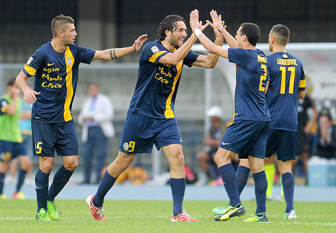Luca Toni of Hellas Verona FC (2nd from left) celebrates after scoring his second goal against AC Milan during their Serie A match at Stadio Marc'Antonio Bentegodi in Verona, on Saturday