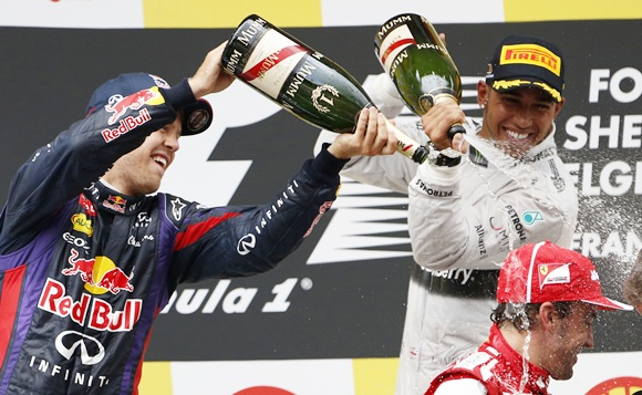Winner Red Bull Formula One driver Sebastian Vettel of Germany (left) and third-placed Mercedes Formula One driver Lewis Hamilton pour champagne on second-placed Fernando Alonso