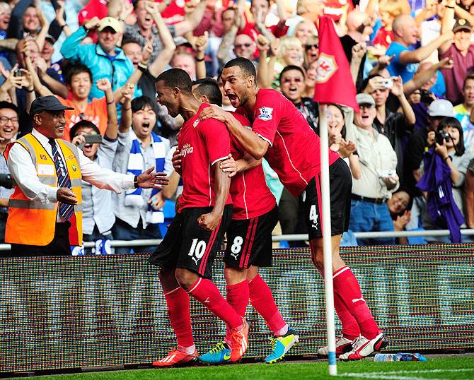 Cardiff City scorers Fraizer Campbell (left) and teammates lead the celebrations after the third Cardiff goal against Manchester City at Cardiff City Stadium in Cardiff, Wales, on Sunday