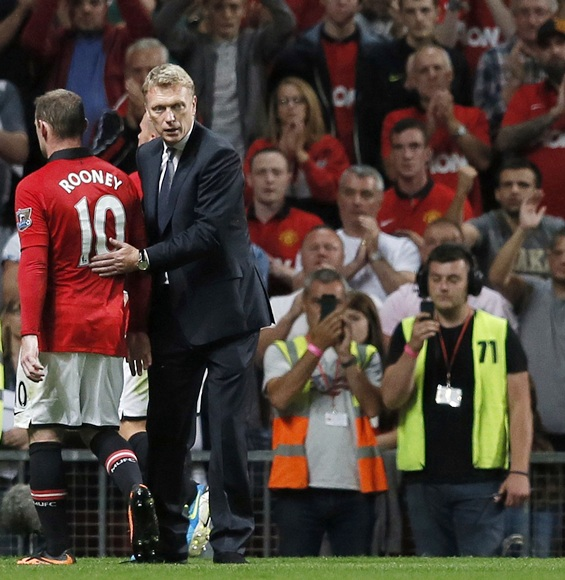 Manchester United's manager David Moyes pats Wayne Rooney (left)
