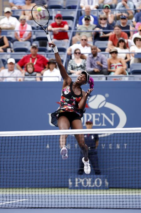 Venus Williams of the US jumps to make a return to Kirsten Flipkens of Belgium