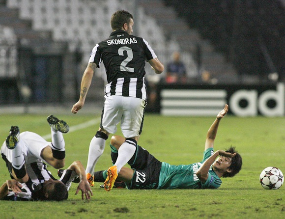 PAOK Salonika's Giannis Skondras (centre) is tackled by Schalke 04's Atsuto Uchida (right)