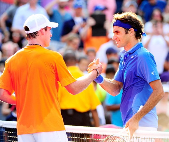 Roger Federer (right) of Switzerland shakes hands at the net with Grega Zemlja of Slovenia