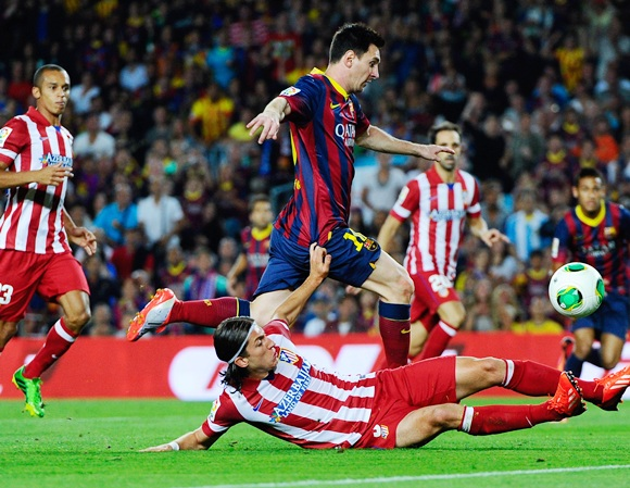Lionel Messi of FC Barcelona duels for the ball with Filipe Luis of Atletico de Madrid