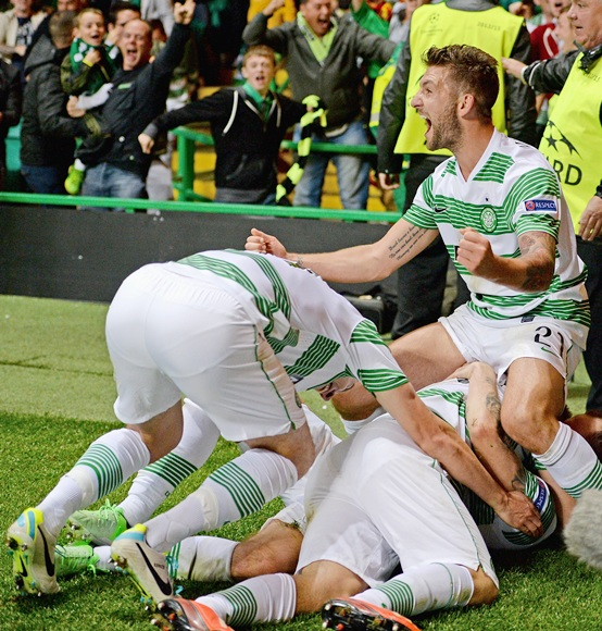 Players surround James Forrest of Celtic after he scored the winning goal