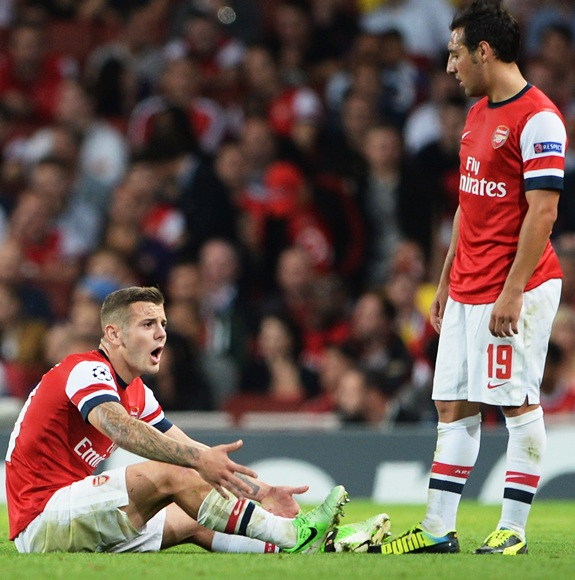Jack Wilshere of Arsenal clutches his ankle after a tackle