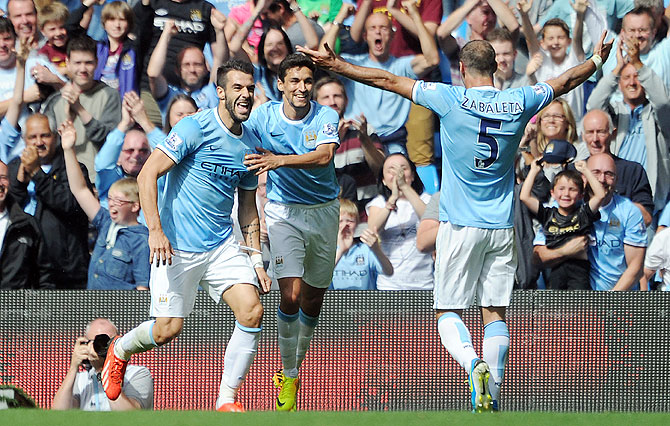 Manchester City's Alvaro Negredo (left) celebrates with teammates Jesus Navas and Pablo Zabaleta after scoring the opening goal of the Barclays Premier League match against