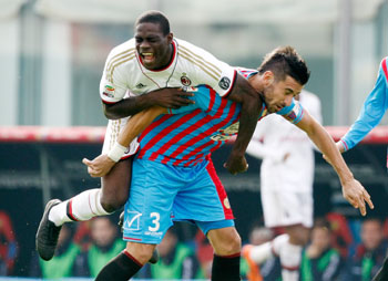 Nicolas Spolli (right) of Catania challenges Mario Balotelli of Milan during their Serie A match at Stadio Angelo Massimino in Catania on Sunday