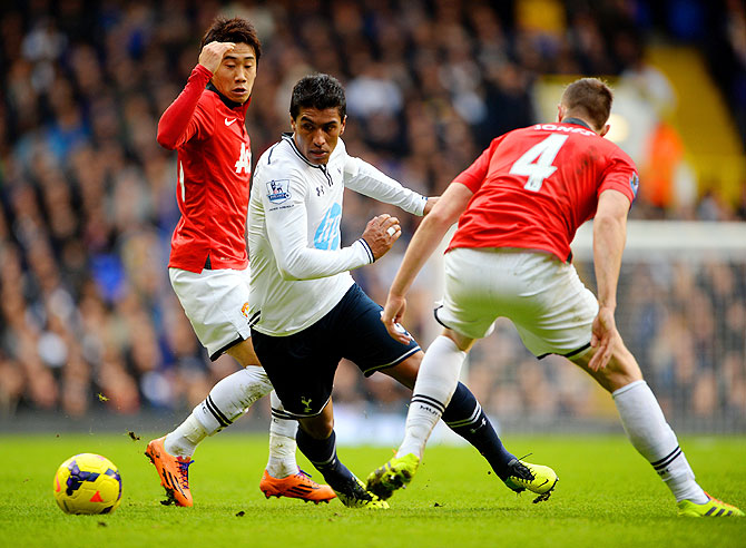 Paulinho of Tottenham Hotspur dribbles past Shinji Kagawa and Phil Jones of Manchester United during their English Premier League match at White Hart Lane in London Sunday