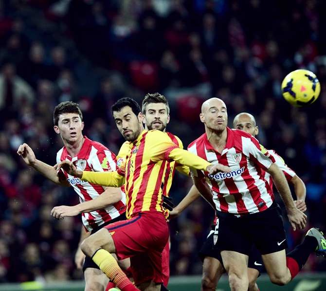 Athletic Bilbao's Aymeric Laporte (left) and Mikel Rico (right) challenge Barcelona's Cesc Fabregas (second left) and Gerard Pique
