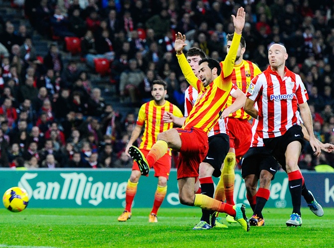 Sergio Busquets of FC Barcelona is brought down by Iker Muniain of Athletic Club