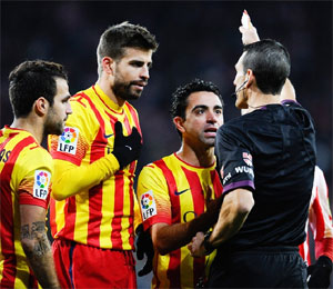 Cesc Fabregas, Gerard Pique, Xavi Hernandez and Andres Iniesta of FC Barcelona argue with the Referee Juan Martinez Munuera