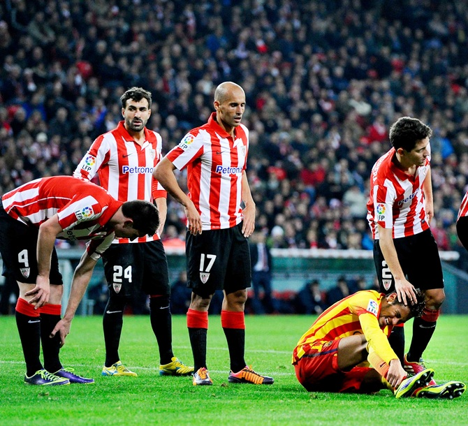 Neymar of FC Barcelona sits on the pitch among Athletic Club players