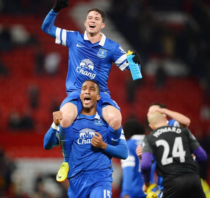 Bryan Oviedo of Everton (top) celebrates with team-mate Sylvain Distin