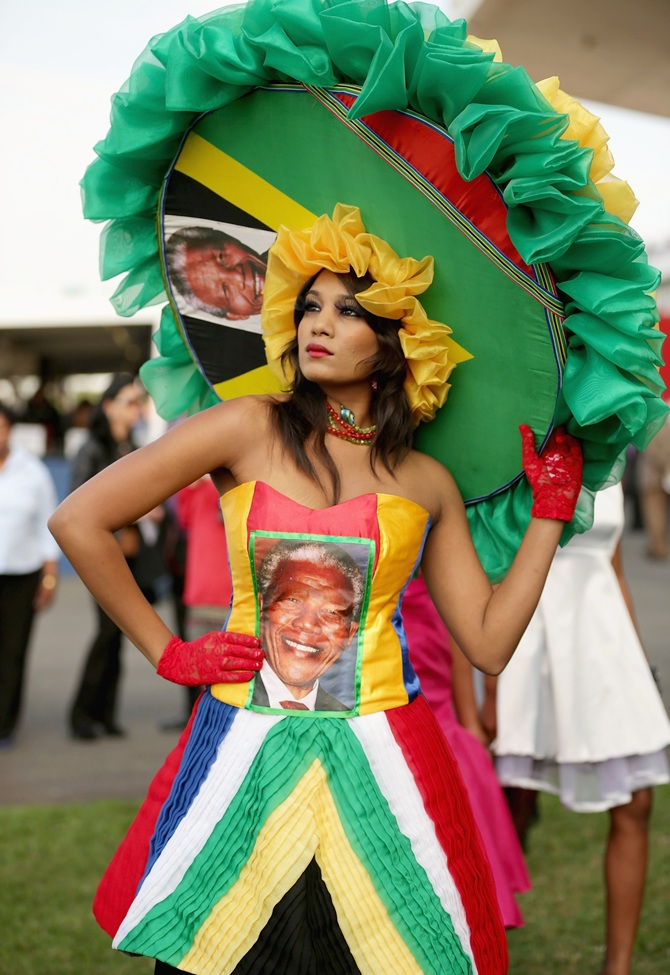 A racegoer dons a Nelson Mandela-inspired dress and hat while participating in a fashion competition
