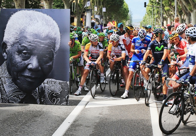 The peloton waits behind a large picture commemorating the birthday of former South African President Nelson Mandela