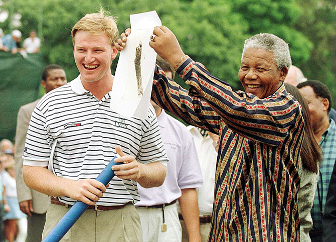 Ernie Els and President Nelson Mandela of South Africa share a laugh as Mandela shows a sketching of Els to the crowd before the final round of the Alfred Dunhill South African PGA Championship at Houghton Golf Club, Johannesburg, South Africa in February 1996