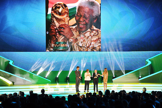 A tribute to Nelson Mandela is displayed on a screen as FIFA President Sepp Blatter, Brazil President Dilma Rousseff and hosts Fernanda Lima and Rodrigo Hilbert stand on stage before the final draw for the 2014 FIFA World Cup at Costa do Sauipe Resort, Bahia, Brazil on Friday
