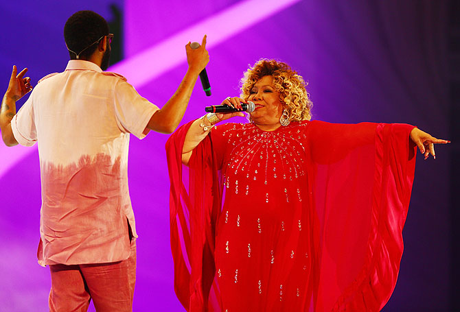 Alcione and Emicida perform on stage before the draw on Friday
