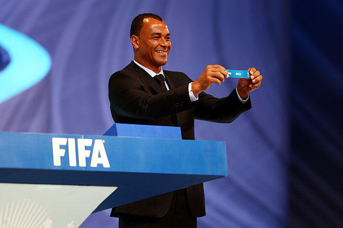 Draw assistant Cafu holds up the name of Brazil during the draw