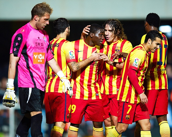 Dongou (second left) of Barcelona celebrates with his teammate Carles Puyol