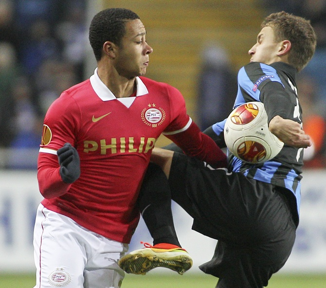 PSV Eindhoven's   Memphis Depay (left) fights for the ball with Chernomorets Odessa's Ivan Bobko