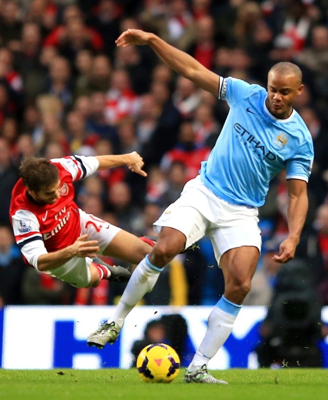 Mathieu Flamini of Arsenal clashes with Vincent Kompany of Manchester City