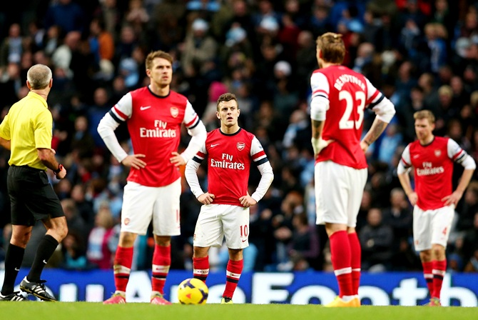 Aaron Ramsey, Jack Wilshere and Nicklas Bendtner of Arsenal stand dejected