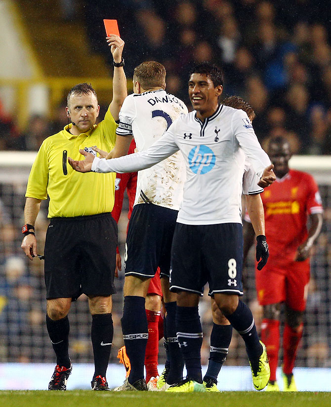 Referee Jonathan Moss shows Paulinho of Tottenham Hotspur a red card for a foul on Luis Suarez of Liverpool on Sunday