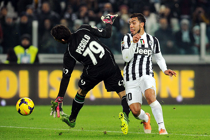 Carlos Tevez of Juventus (right) scores past goalkeeper Gianluca Pegolo of US Sassuolo Calcio
