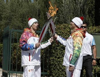 First torchbearer Yiannis Antoniou relays the flame to second torchbearer Alexander Ovechkin of Russia outside the Pierre de Coubertin monument during the torch relay September 29, 2013 in Olympia, Greece