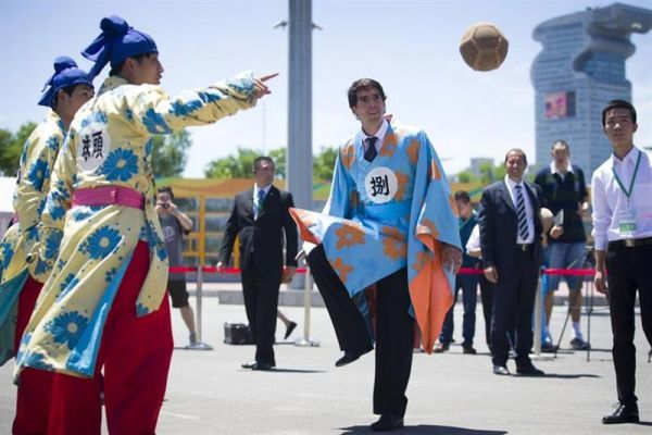 Brazilian soccer player Kaka, wearing a traditional Chinese costume, kicks a ball during a traditional Chinese ball game called Cuju