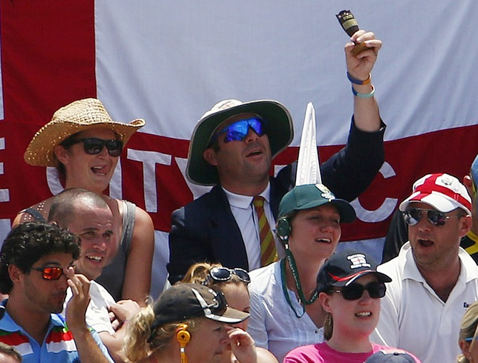 A fan from the Barmy Army holds up an Ashes replica urn
