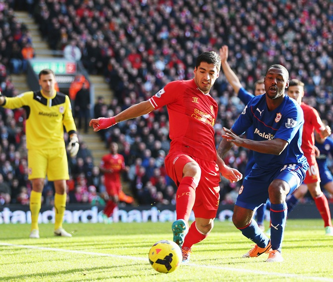 Luis Suarez (left) of Liverpool and Kevin Theophile-Catherine (right) of Cardiff City challenge for the ball